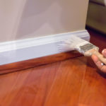 A house painter paints the baseboard of a residential home with white paint.  rr